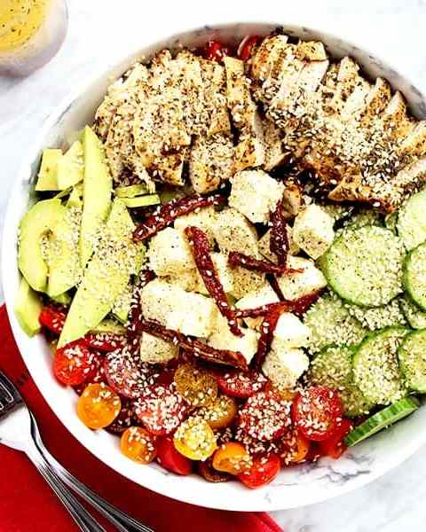 Top down shot of grilled chicken salad on a white tabletop