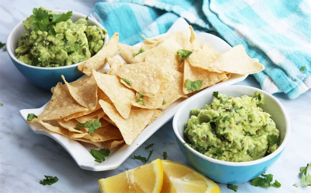 Two bowls of jalapeno guacamole next to tortilla chips