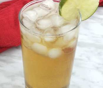 A spiced rum cocktail garnished with a slice of lime.
