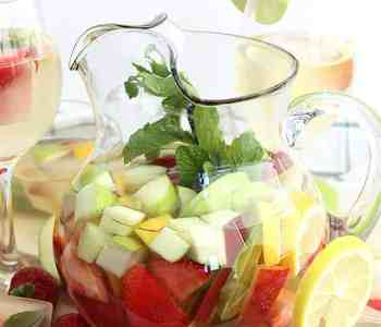 White wine sangria in a jug filled with fresh fruit and mint leaves