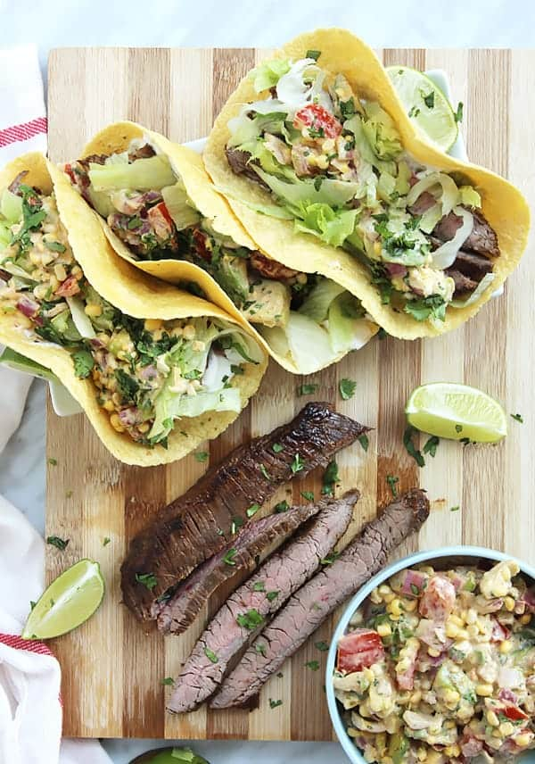 beef recipes for taco Tuesday. Pieces of carne asada in between dressed tacos and a taco dip