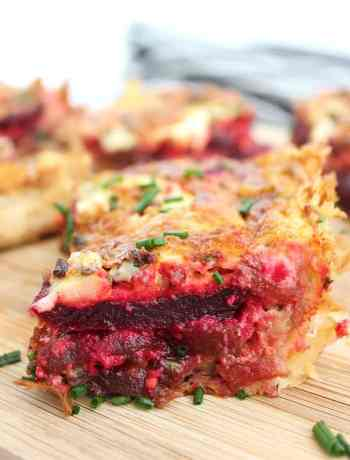 A slice of beetroot tart on a wooden chopping board