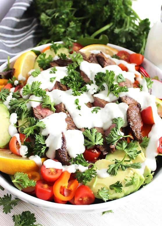Steak salad in a large white bowl with fresh herb garnish