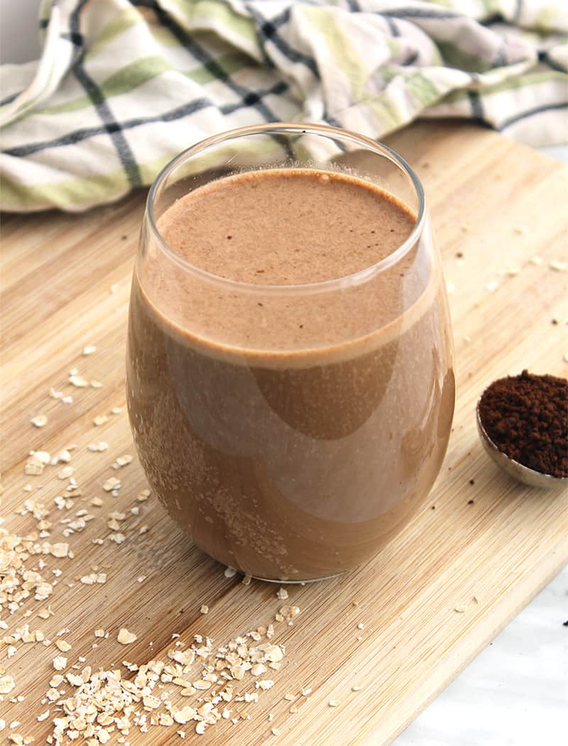 A coffee smoothie in a glass on a wooden chopping board