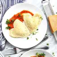Tow pieces of heart shaped ravioli on a white plate with homemade sauce