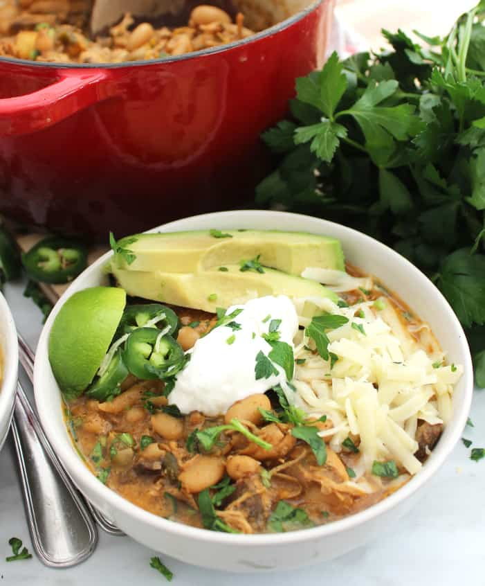 White bean chili topped with avocado, shredded cheese, sour cream and jalapenos