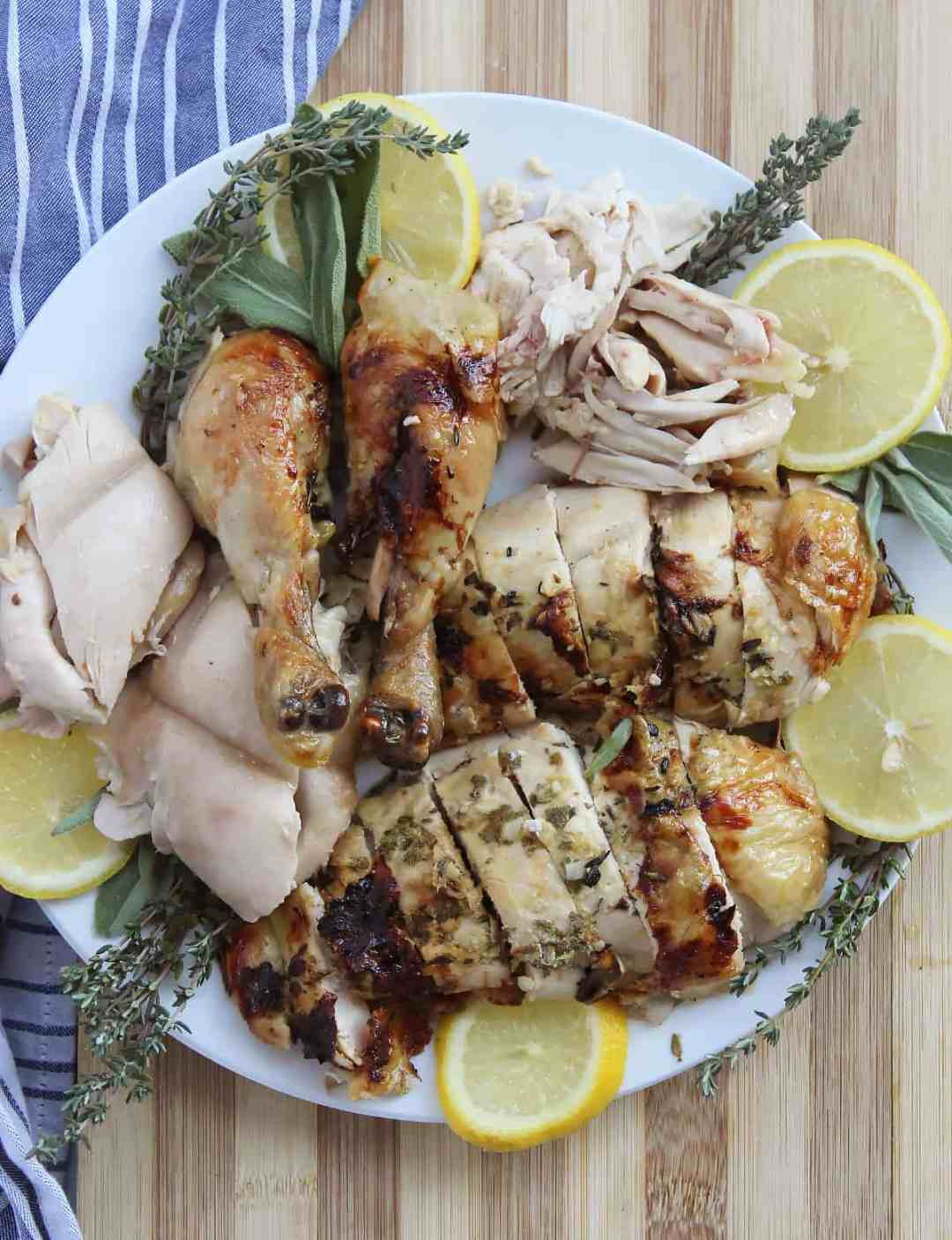 Pieces of slow roasted chicken on a plate with lemon and herbs