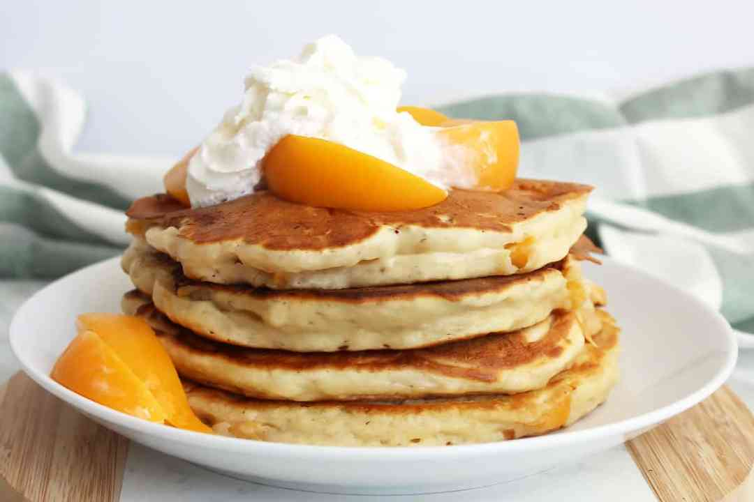 A stack of peach pancakes topped with whipped cream and peach slices