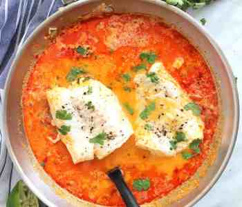 Overhead shot of poached fish in a skillet with fresh cilantro garnish