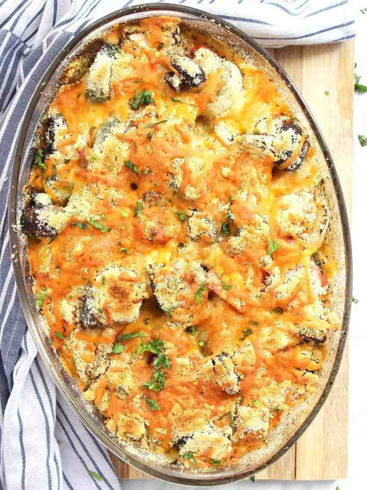 Vegetable crumble in a glass baking dish on a wooden chopping board