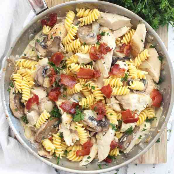A silver skillet with chicken and mushroom pasta on a wooden chopping board.