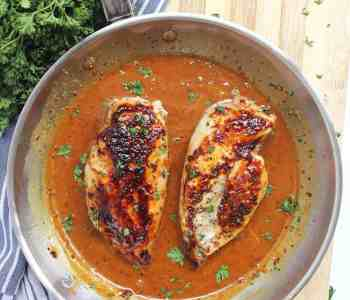 Two chicken breasts in honey and mustard sauce in a skillet.