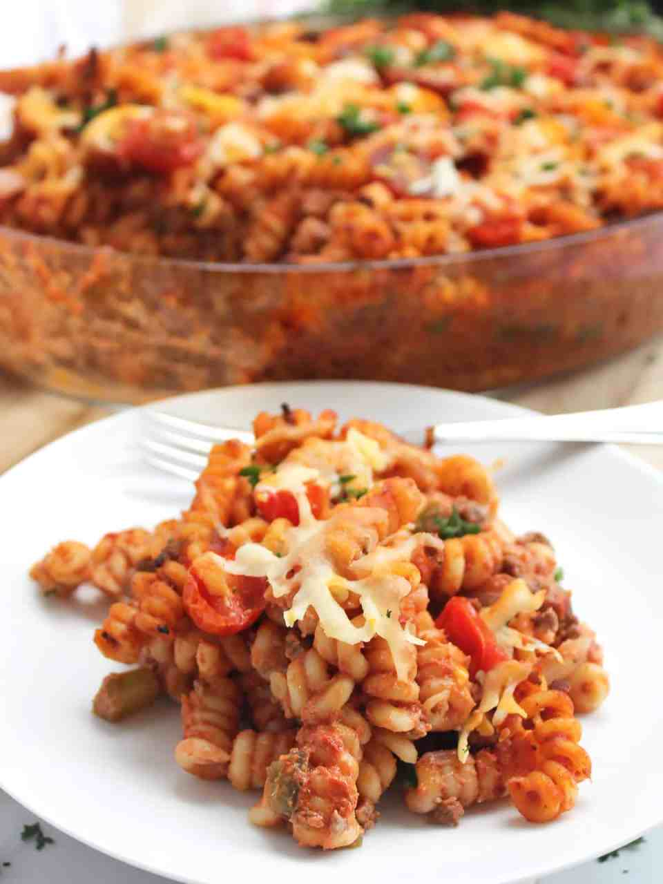 A serving of ground beef pasta bake on a white plate with a fork.