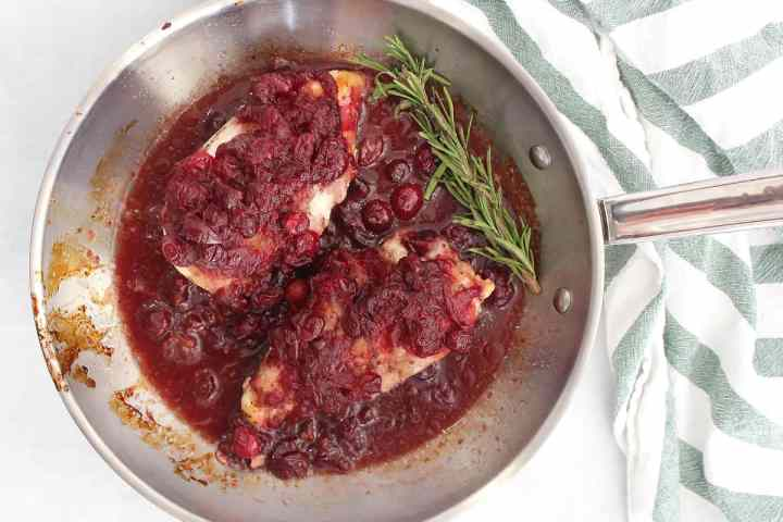 Two chicken breasts in a skillet covered with cranberry sauce and garnished with a sprig of rosemary.