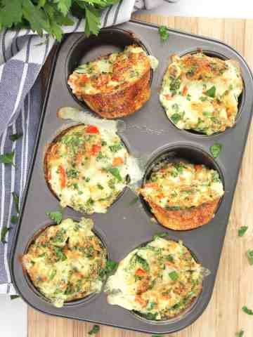 Overhead shot of the egg white bites in a muffin tin next to a bunch of fresh herbs.