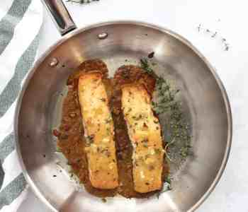 Two honey mustard salmon fillets in a skillet with fresh thyme sprigs.