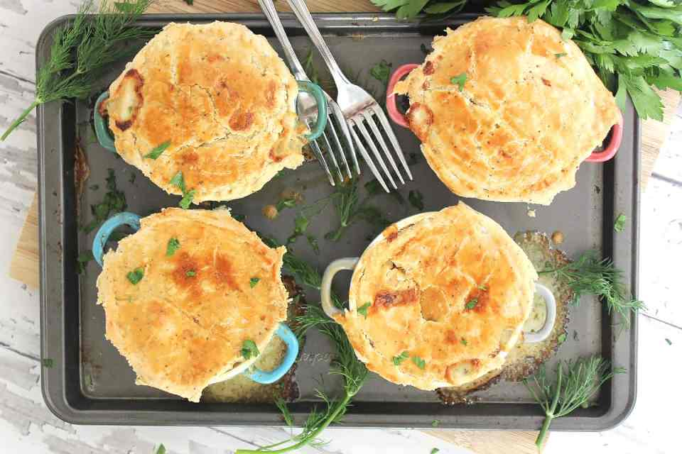 Overhead shot of four baked salmon pies on a baking sheet with fresh dill.