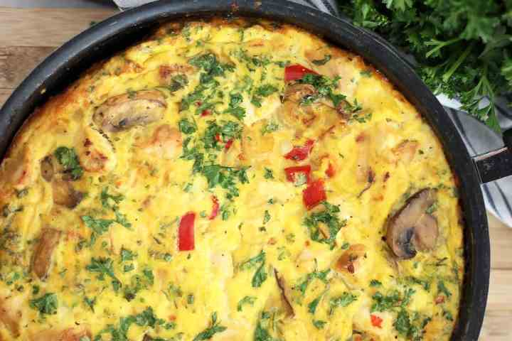 Close up of the chicken and vegetable frittata in a black skillet.