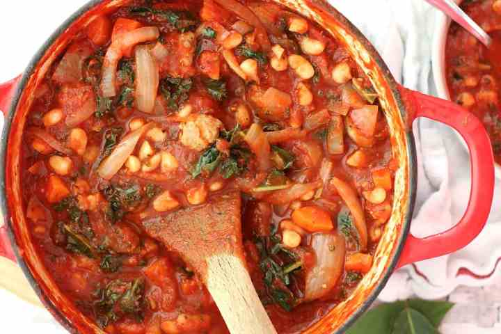 Close up of the soup in a red pot with a wooden spoon.
