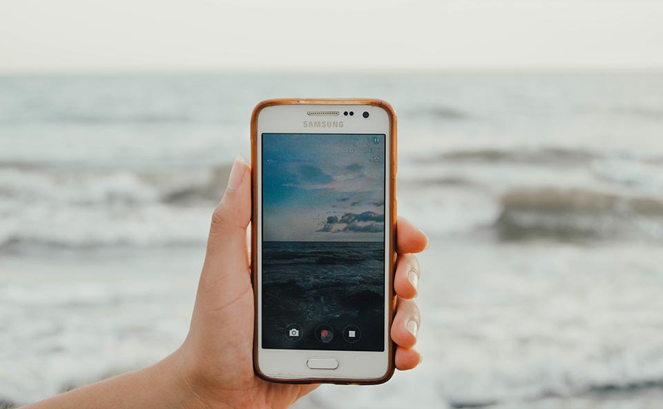 Someone taking a picture of the sea, picture that can be used for stock later on.