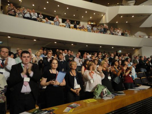 Delegates stand to applaud Rev David Latimer as he gets up onto the stage