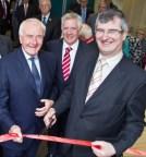Tom Eliott wielding scissors at the opening of David McNarry's Saintfield Advice Centre Opening