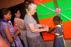 Slum2School beneficiary presenting the scissors to Mrs Jean Obi, the chair person for the commissioning.