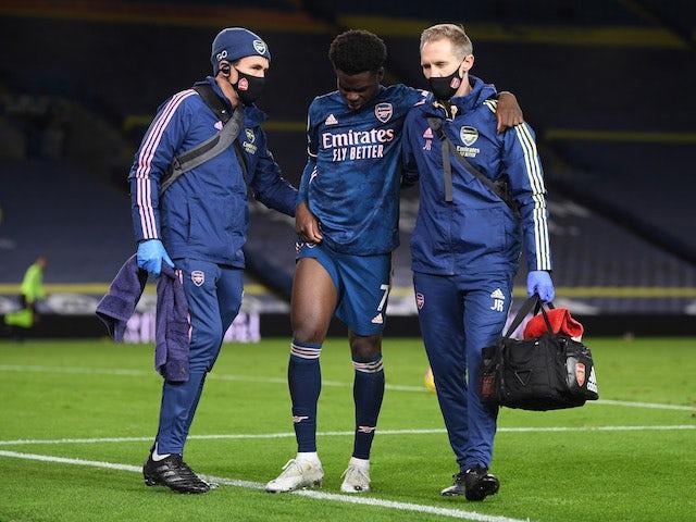 Arsenal's Bukayo Saka is helped off after sustaining an injury on November 22, 2020