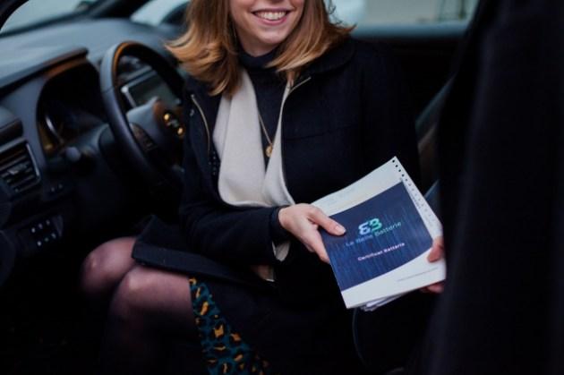 Remise du certificat La Belle Batterie à une cliente assise dans sa voiture électrique