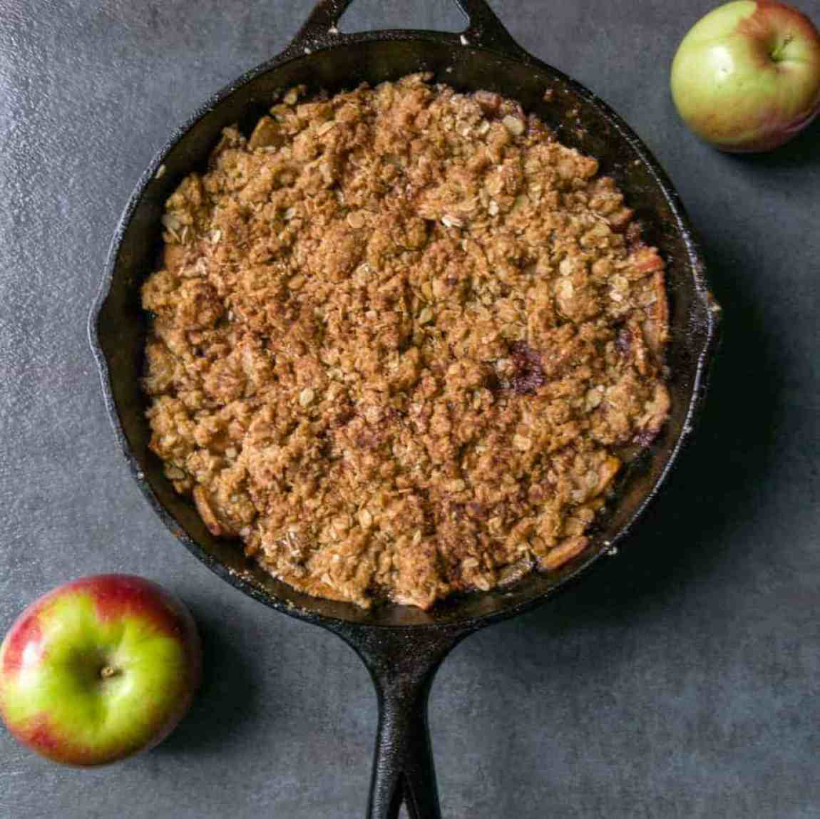 apple crumble in a cast iron skillet on counter top with two whole apples to make the perfect apple dessert recipe for the next camping trip