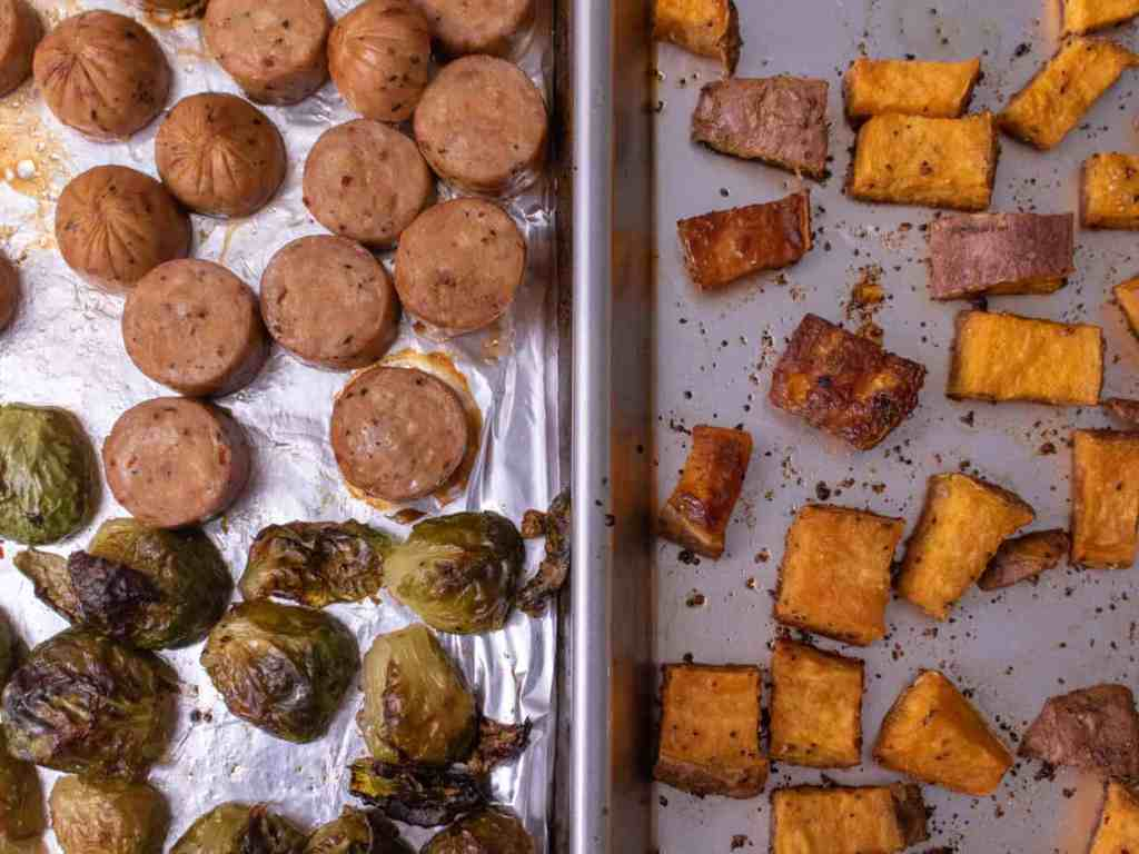 Overhead shot, roasted sweet potatoes on the right and chicken sausage and roasted brussel sprouts on the left, both on sheet trays.