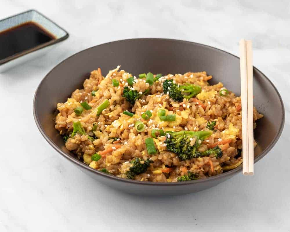Fried rice in a brown bowl with soy sauce and chopsticks in the background