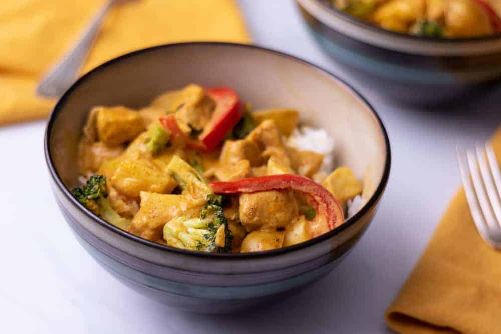 A bowl of yellow curry with chicken, broccoli and red peppers over white rice.
