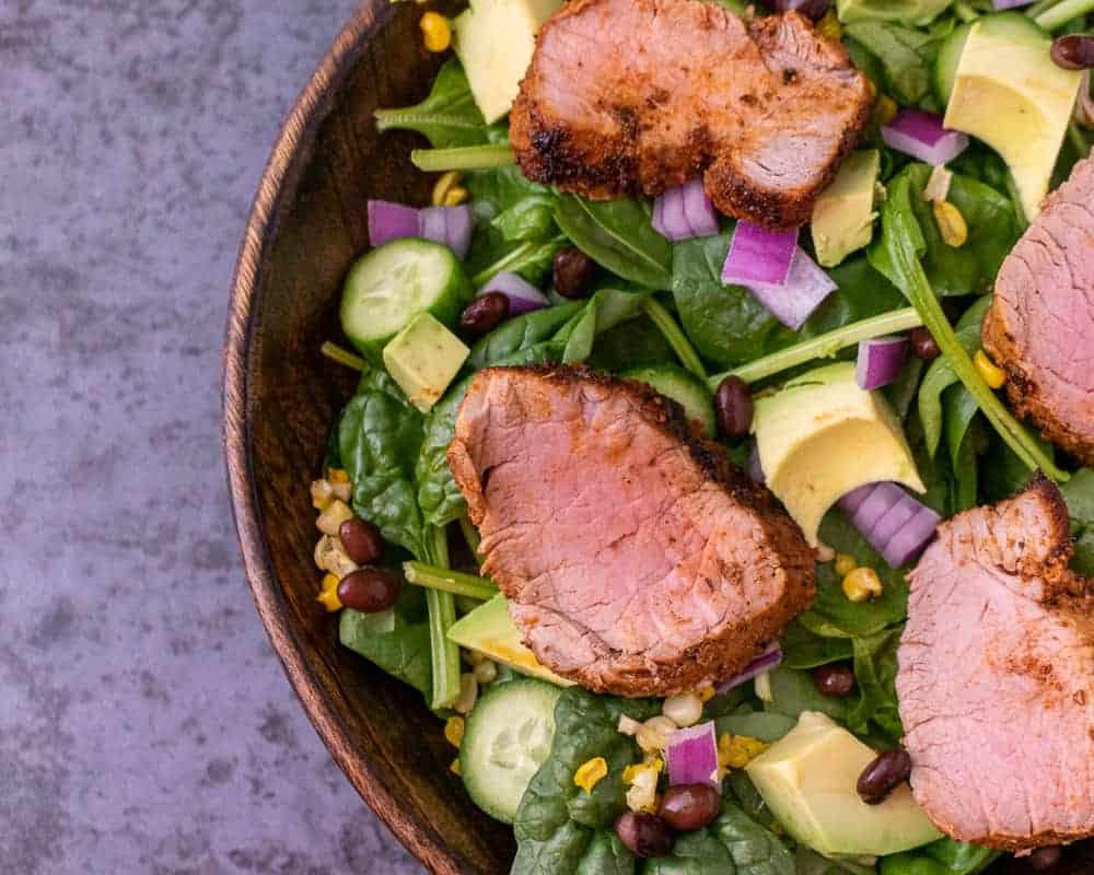 Close up of cajun pork tenderloin spinach salad in a wooden bowl