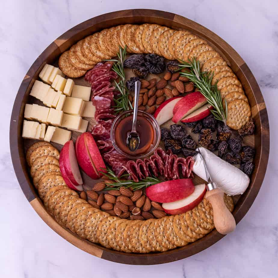 Overhead view of Thanksgiving cheese plate with cheddar cheese, goat cheese, rosemary, crackers, honey, almonds, dried figs and fresh apples