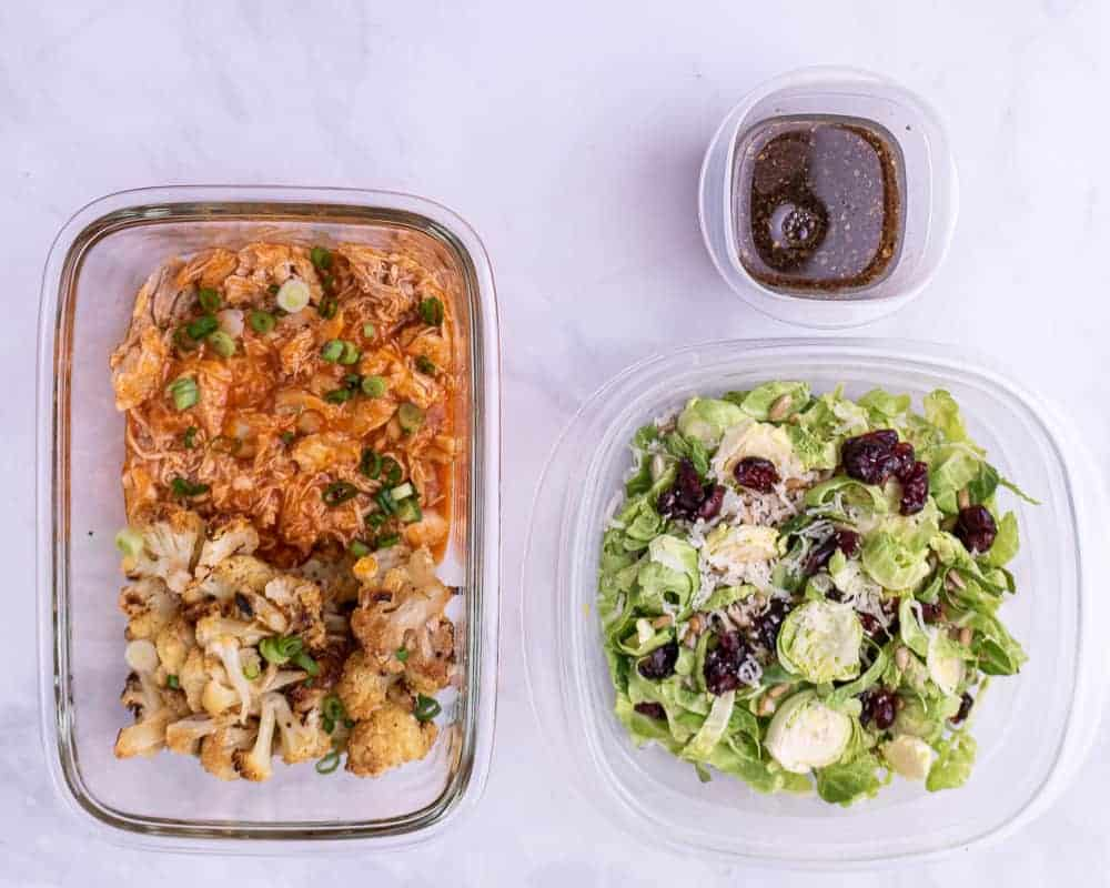 Shredded buffalo chicken in a container with roasted cauliflower next to a food storage container full of brussels sprout meal prep salad.