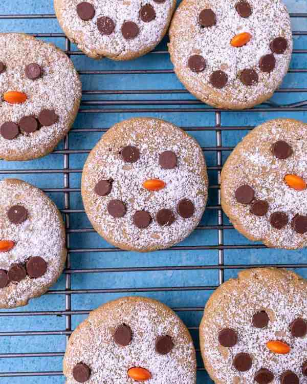 A close up of snowman cookies on a blue background on a wire rack
