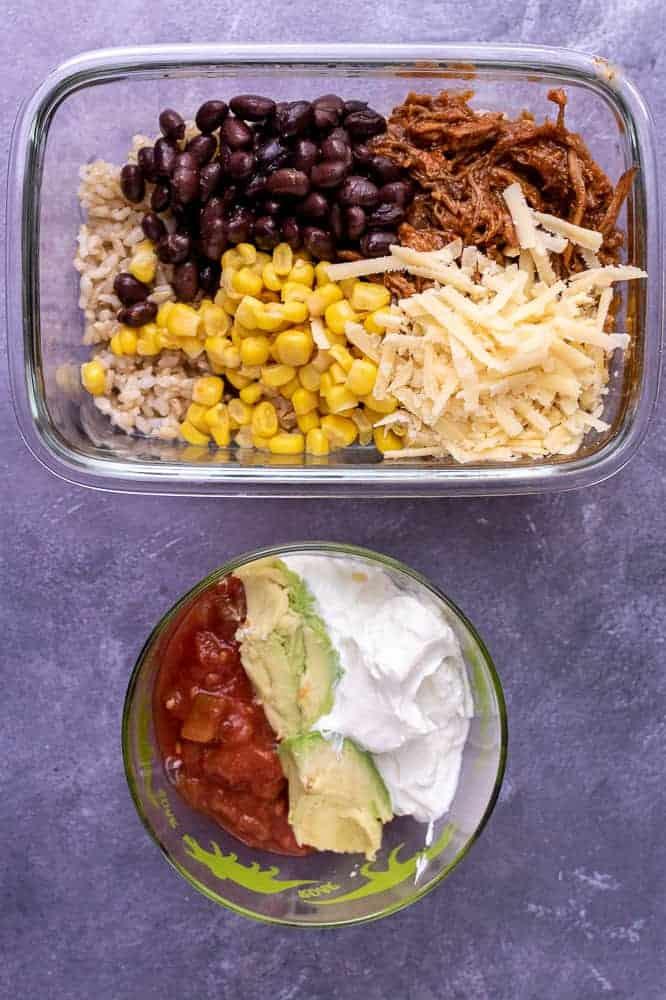 A final photo of the pork burrito bowl base next to a separate container of sour cream, avocado and salsa.