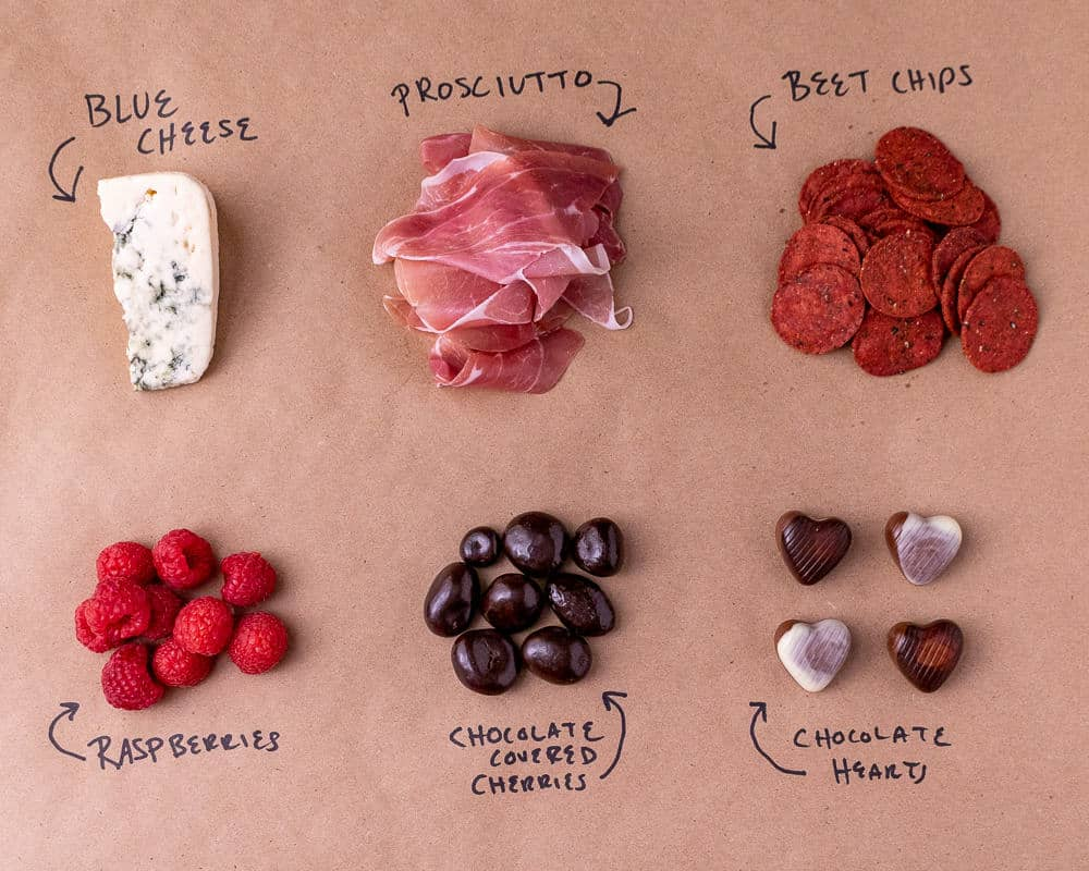 The ingredients for the cheese plate on a brown background laid out