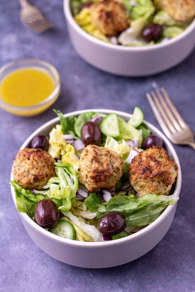 2 bowls of greek chicken salad with forks and salad dressing.