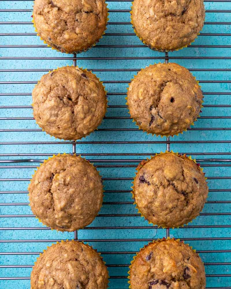 Cooked muffins in two parallel rows on a wire rack on a blue background.