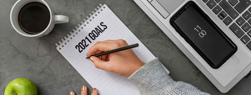 crop unrecognizable woman writing goals for upcoming year in notepad