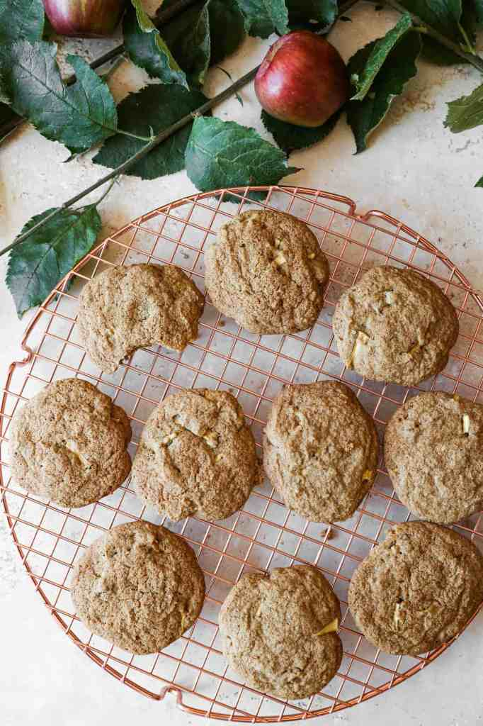 a cooling rack of gluten free apple spice cookies surrounded by apples and cinnamon sticks