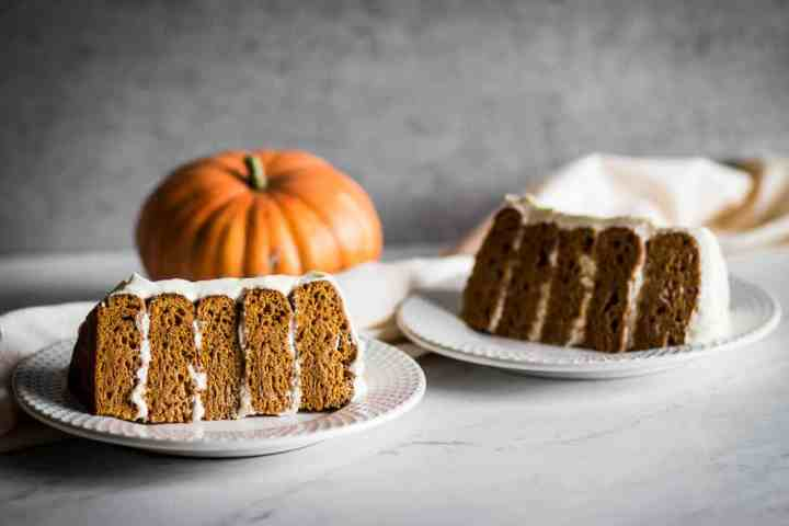 Two slices of homemade gluten free pumpkin cake with cream cheese frosting