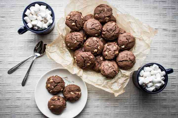 a plate of gluten free hot cocoa cookies with mugs of hot chocolate