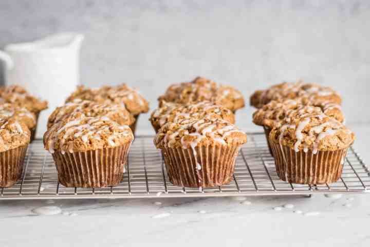 gluten free apple carrot muffins with icing drizzled over them