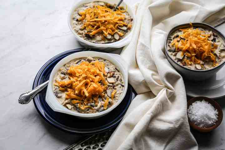 three bowls of instant pot wild rice, chicken and mushrooms with shredded cheddar cheese on top
