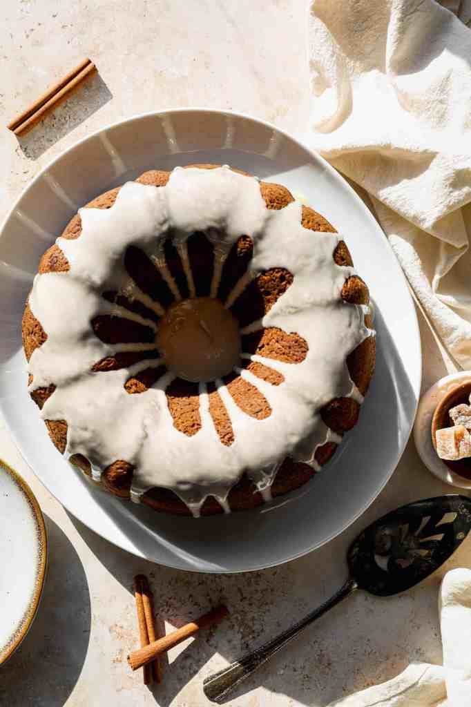 a gluten free gingerbread bundt cake with vanilla glaze on a white plate