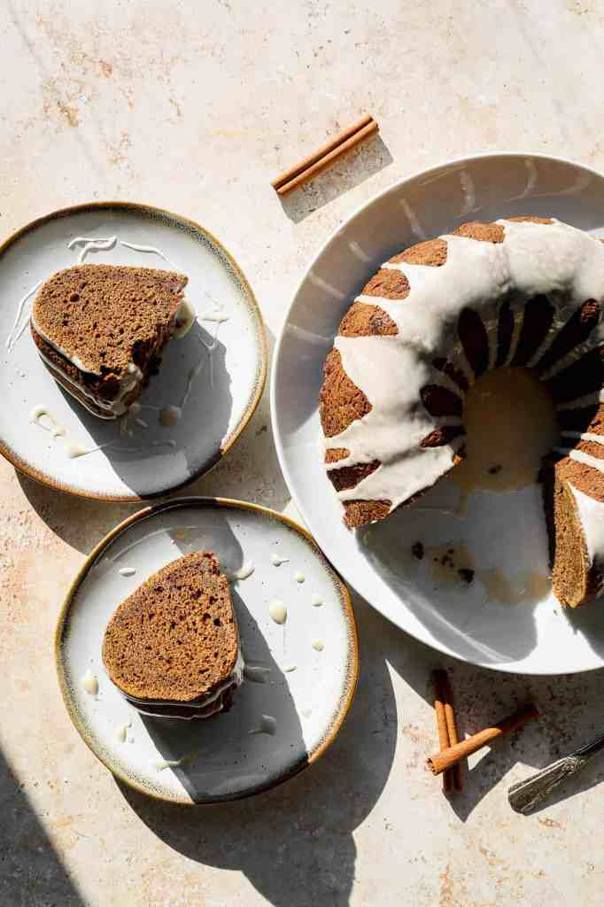a gluten free gingerbread bundt cake with vanilla glaze with two slices on plates