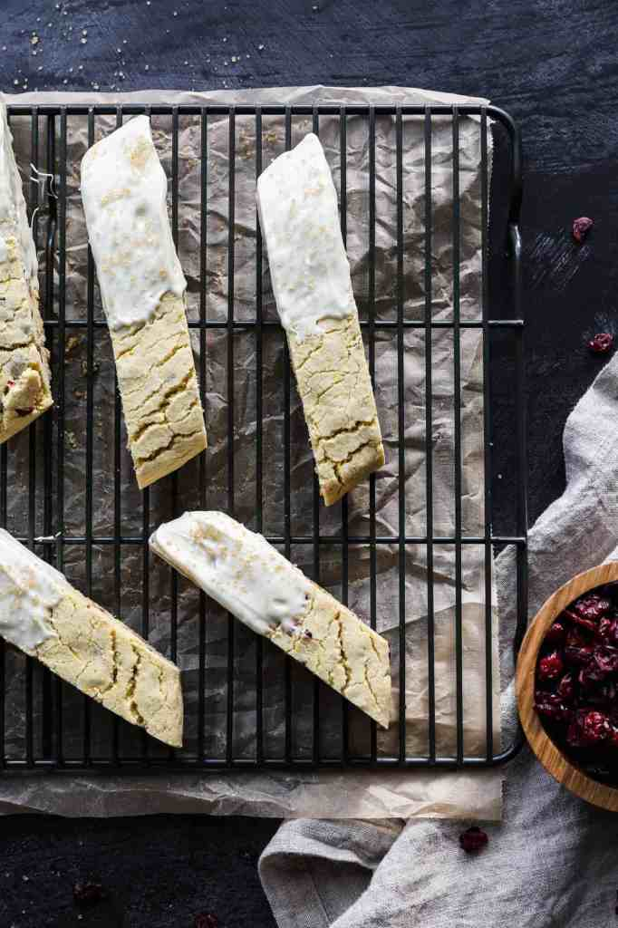 a cooling rack with gluten free orange cranberry biscotti dipped in white chocolate and sprinkled with sugar crystals